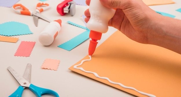 Mão humana, aplicando, cola branca, ligado, laranja, papel, com, scissor, e, grampeador Foto gratuita