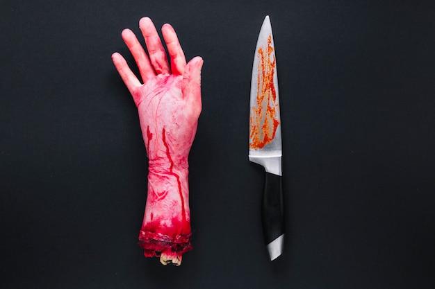 Mão humana artificial no sangue e faca Foto gratuita