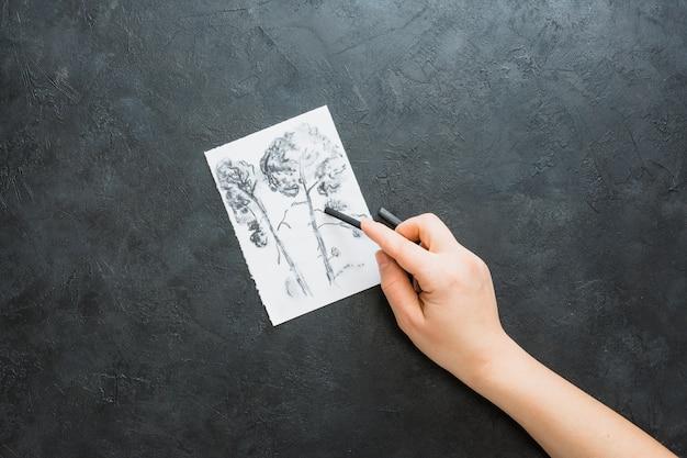 Mão humana, desenho, com, vara carvão, sobre, experiência preta Foto gratuita