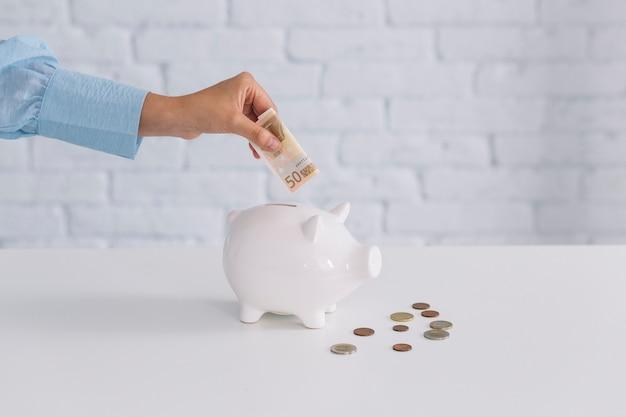 Mão humana, inserindo notas de cinquenta euros em piggybank na mesa Foto gratuita