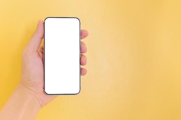 Mão humana que guarda o smartphone com fundo de tela branco. Foto Premium