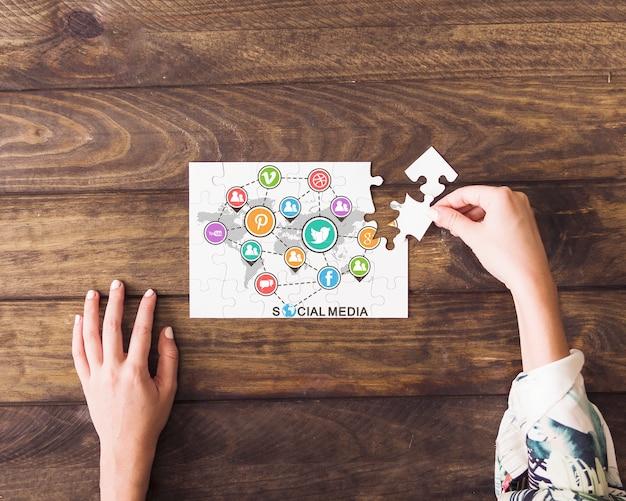 Mão humana, resolvendo, social, mídia, ícone's, jigsaw puzzle Foto gratuita