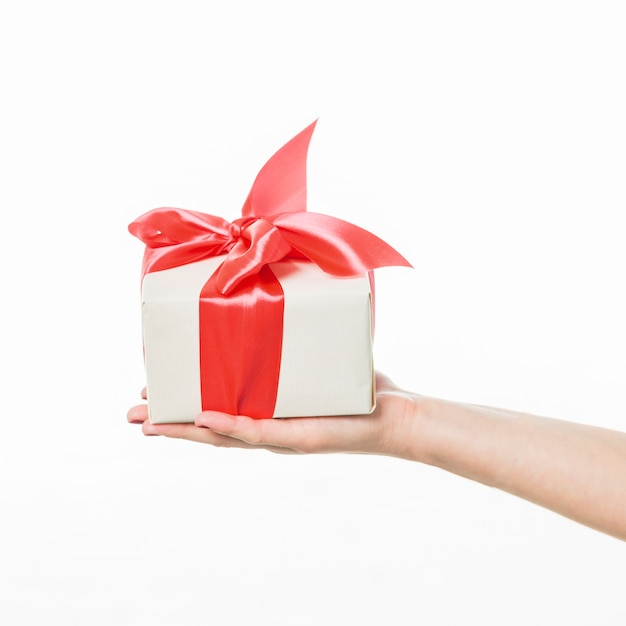 Mão humana segurando a caixa de presente em fundo branco Foto gratuita