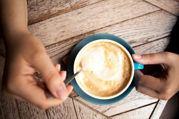 Mão humana segurando a colher de café e mexer o café quente na mesa de madeira Foto gratuita