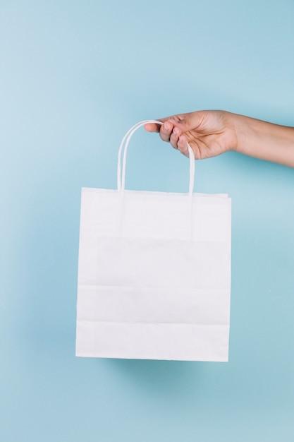 Mão humana segurando sacola de papel Foto gratuita
