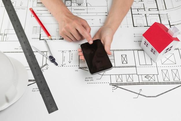Mão humana, usando, cellphone, sobre, blueprint, em, local trabalho Foto gratuita