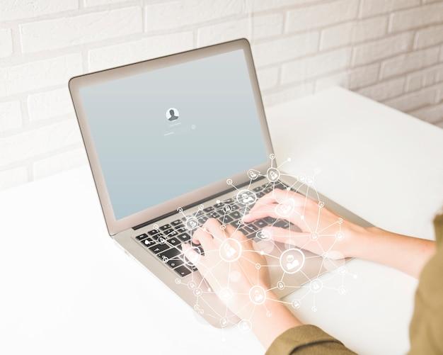 Mão humana usando laptop com efeito de camada digital Foto gratuita