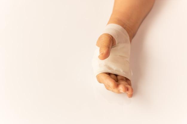 Mão idosa da mulher ferida com a atadura na tabela branca no hospital. Foto Premium