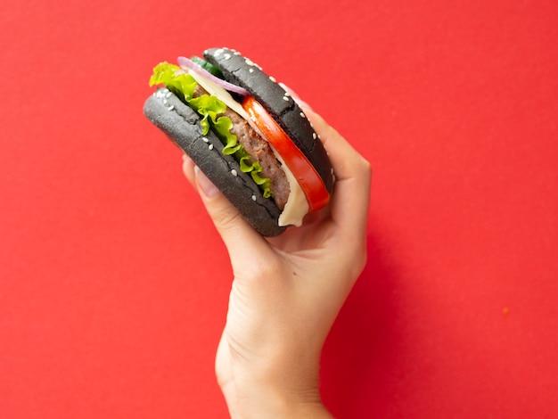 Mão levantando hambúrguer saboroso com fundo vermelho Foto gratuita