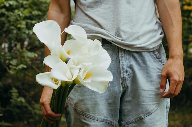 Mão masculina com flores de lírios Foto Premium