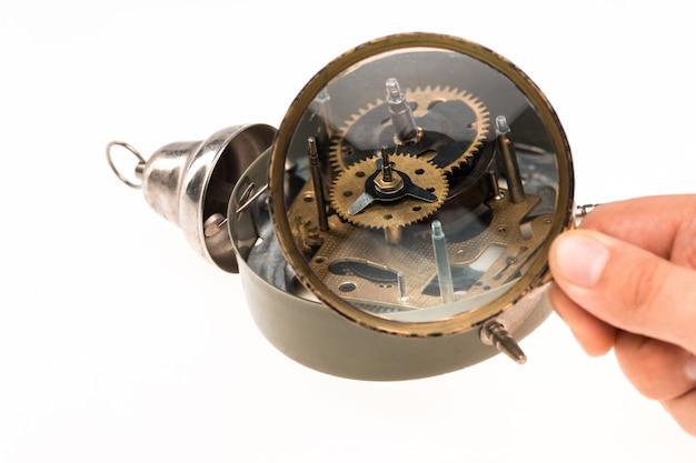 Mão masculina com lupa e relógio Foto gratuita