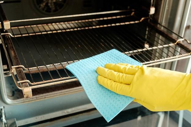 Mão masculina com luvas de limpeza do forno Foto Premium