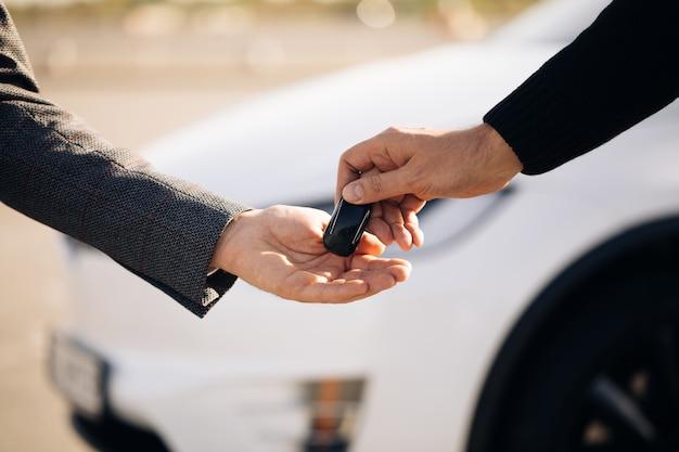 Mão masculina dá as chaves de um carro para mão masculina na concessionária de automóveis close-up Foto Premium