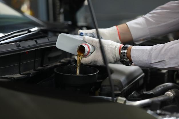 Mão masculina em luvas de proteção brancas com funil Foto Premium