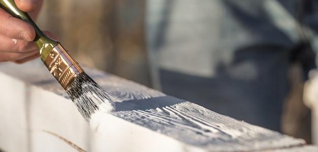 Mão masculina pinta com tinta branca na madeira Foto gratuita