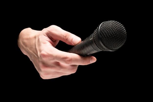 Mão masculina que guarda o microfone em um fundo preto. Foto Premium
