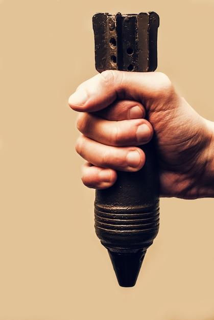 Mão masculina que guarda uma mina oxidada velha do almofariz da segunda guerra mundial. conceito de guerra Foto Premium