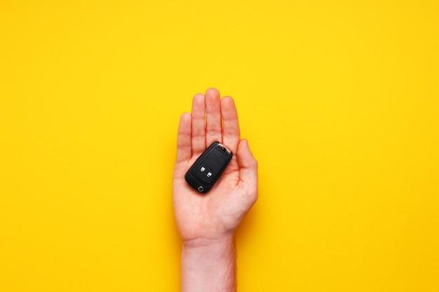 Mão masculina segura as chaves do carro em fundo amarelo. carro-conceito, aluguel de carro, presente, aulas de direção, carta de condução. camada plana, vista superior Foto Premium