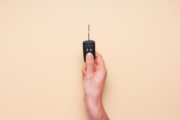 Mão masculina segura as chaves do carro em fundo bege. carro-conceito, aluguel de carro, presente, aulas de direção, carta de condução. camada plana, vista superior Foto Premium