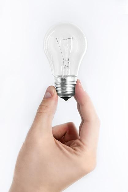 Mão masculina segura uma lâmpada em um fundo branco Foto Premium