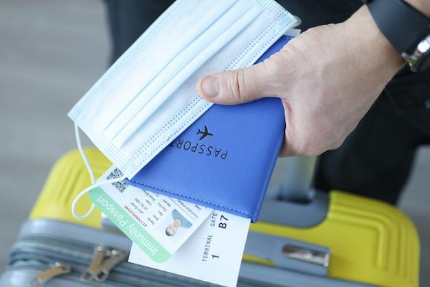 Mão masculina segurando a mala e máscara protetora com passaporte de imunização. viajando durante o covid 19 conceito de pandemia Foto Premium