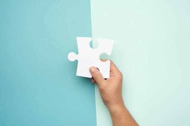Mão masculina segurando grandes quebra-cabeças em branco de papel branco, conceito de negócio Foto Premium