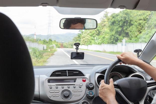 Mão masculina segurando o volante para dirigir o carro na estrada de asfalto Foto Premium