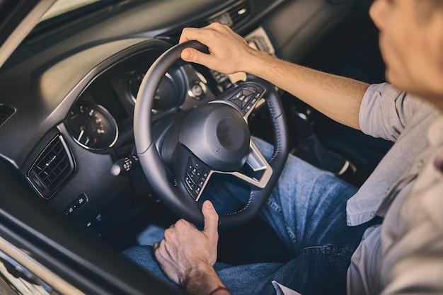 Mão masculina segurando um volante antes de comprar um automóvel novo no showroom Foto Premium