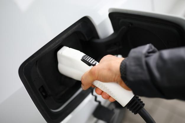 Mão masculina segurar sonda conector carro cobrando estação closeup Foto Premium