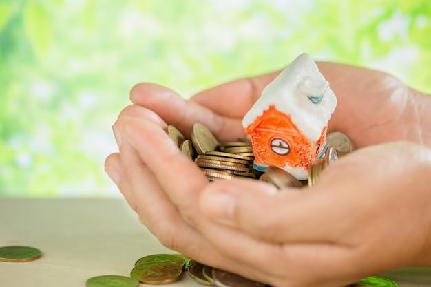 Mão mimada moedas e modelo de pequena casa Foto gratuita