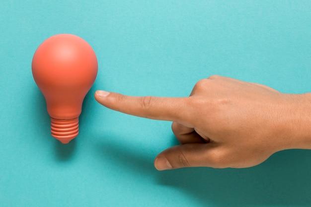 Mão mostrando na lâmpada rosa na superfície colorida Foto gratuita