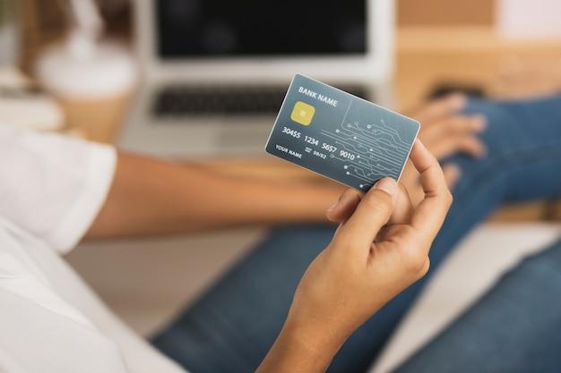 Mão mostrando um cartão de crédito simulado acima Foto gratuita