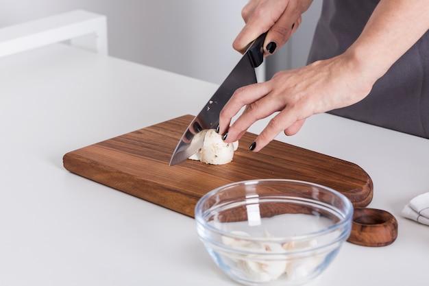 Mão mulher, corte, a, cogumelo, com, faca, ligado, tábua cortante, sobre, a, branca, tabela Foto gratuita