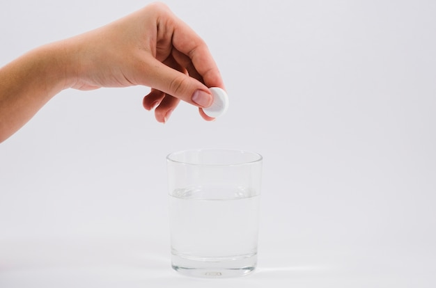 Mão mulher, segurando, branca, pílula, sobre, a, vidro água, contra, cinzento, fundo Foto gratuita