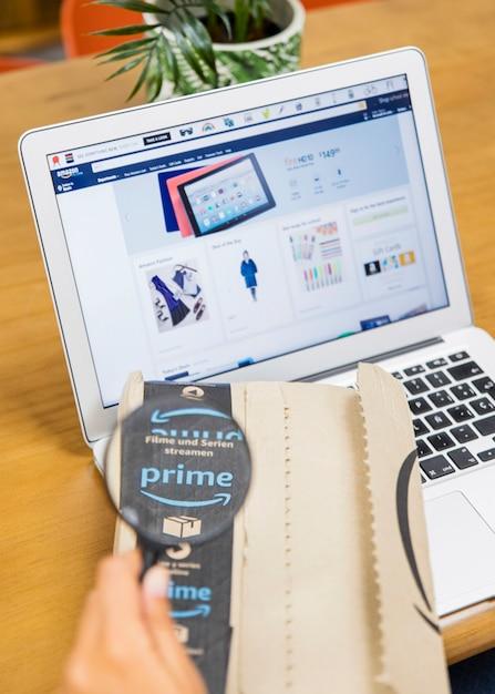 Mão mulher, segurando, magnifier, e, entrega, perto, laptop Foto gratuita