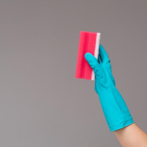 Mão na luva de borracha contém esponja de lavagem de cor Foto Premium
