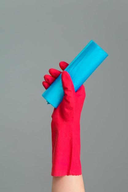 Mão na luva de borracha detém saco de lixo colorido em cinza Foto Premium