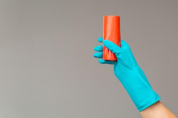 Mão na luva de borracha detém saco de lixo colorido Foto Premium