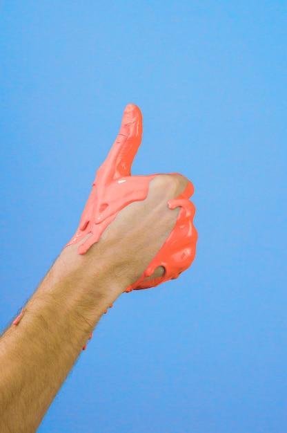 Mão no polegar de tinta vermelha no fundo azul Foto Premium
