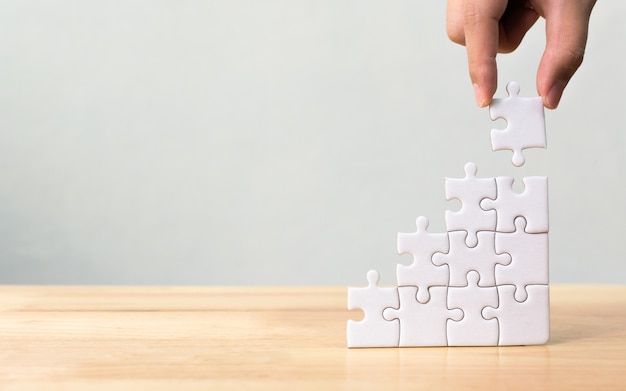 Mão, organizando, jigsaw, quebra-cabeça, empilhando, como, passo, degrau, ligado, tabela madeira Foto Premium