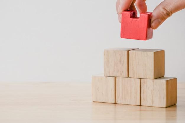 Mão organizando o bloco de madeira Foto Premium