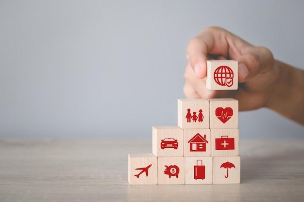 Mão, organizando o empilhamento de blocos de madeira com seguro de ícone: carro, Foto Premium