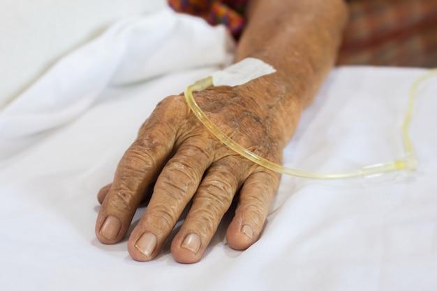 Mão pacientes idosos no hospital com solução salina intravenosa Foto Premium