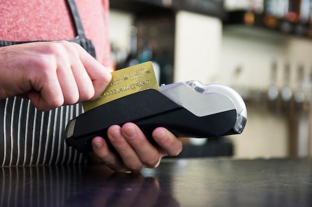 Mão passando o cartão de crédito no dispositivo de leitura de cartão Foto gratuita