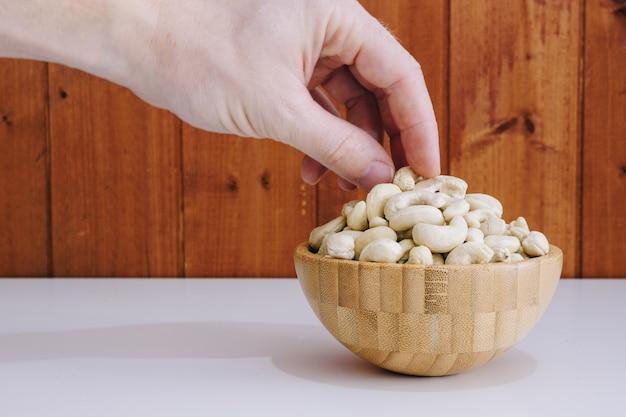 Mão pegando uma castanha de caju Foto Premium