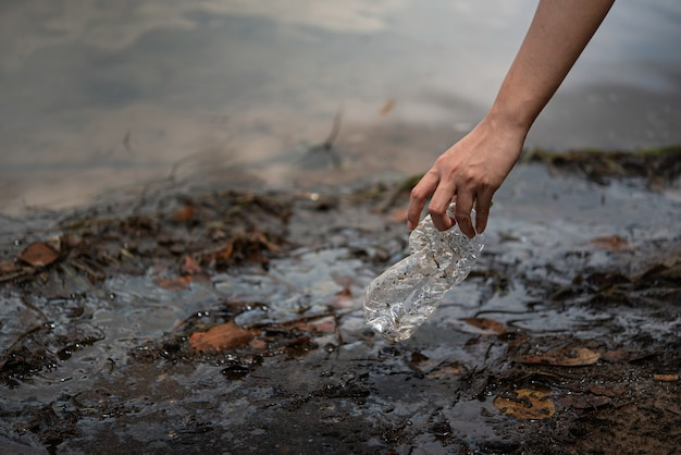 Mão pegar garrafa de plástico da água Foto Premium