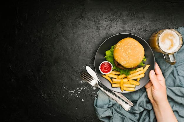 Mão plana leigos segurando o prato com hambúrguer e batatas fritas com copyspace Foto gratuita