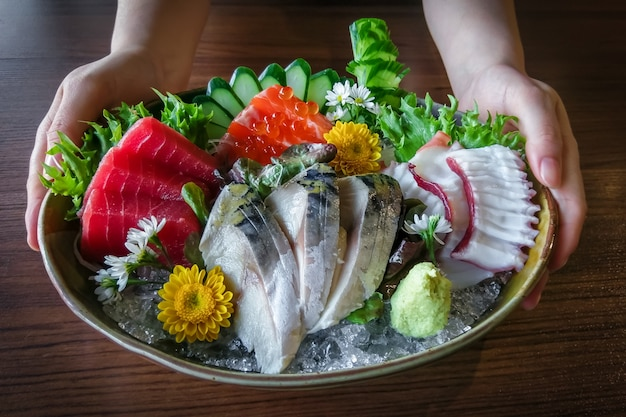 Mão, prato segurando, de, japoneses, sashimi, marisco, jogo Foto Premium