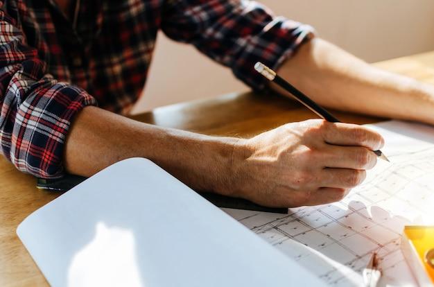 Mão profissional arquiteto, engenheiro ou interior mãos desenhando com blueprint na mesa de trabalho Foto Premium
