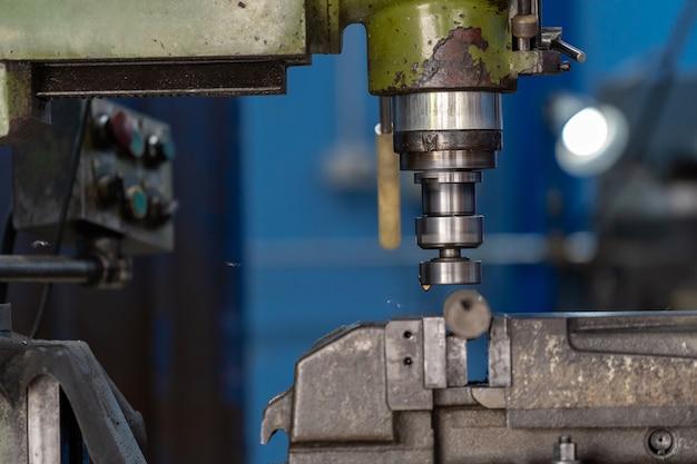 Mão profissional do maquinista que trabalha com a máquina de trituração na fábrica metalúrgica Foto Premium